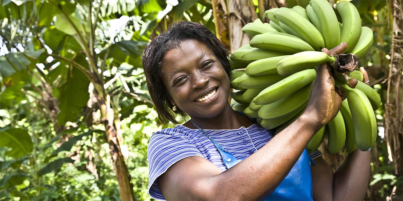 Lachende Frau mit Bananenstaude auf der Schulter