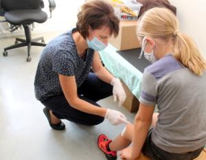 Schulgesundheitsfachkraft Michaela Kellter behandelt eine kleine Schürfwunde.